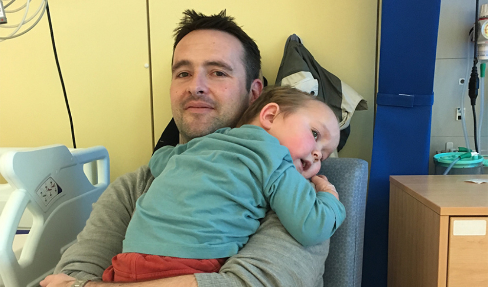 Father holding  a young toddler in a hospital ward