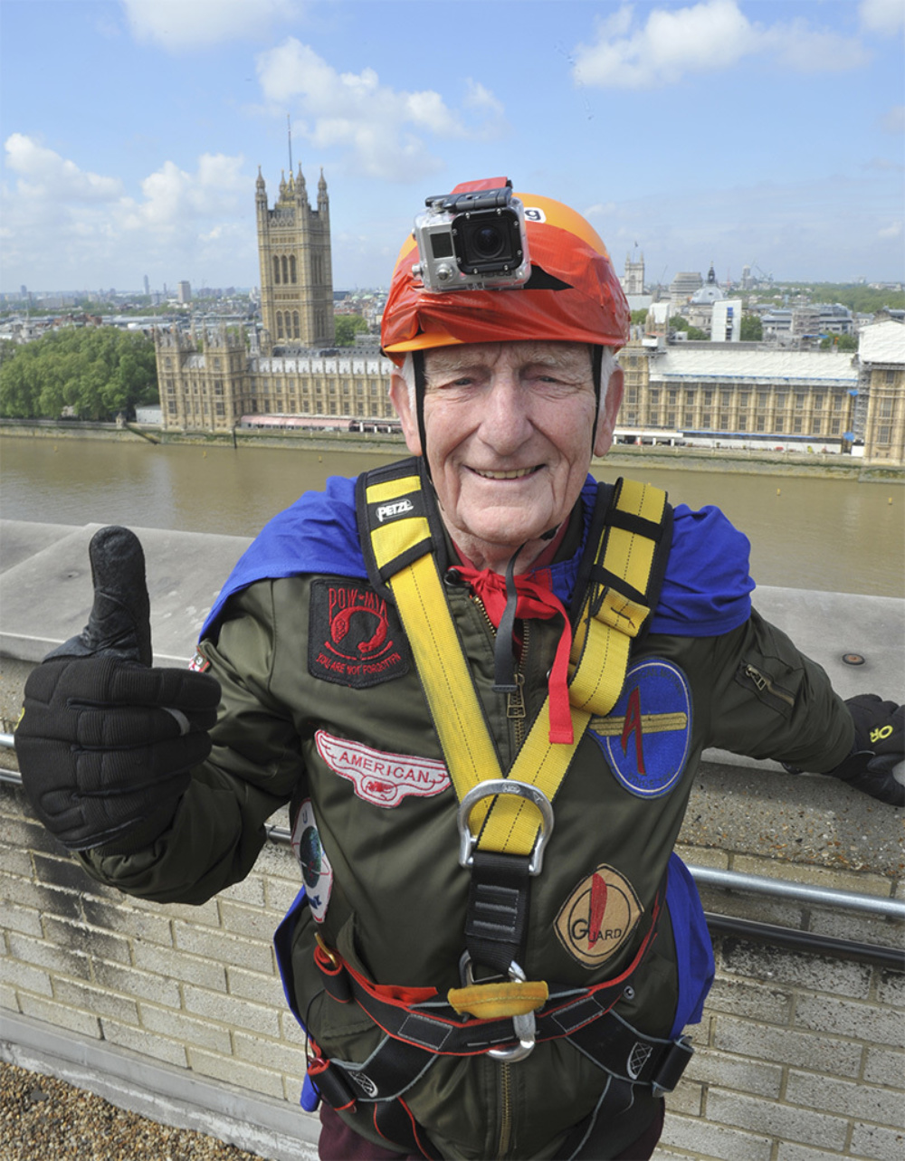 A man on the roof of a 16-story building in daylight, dressed in abseil gear, over looking the Thames and Big Ben