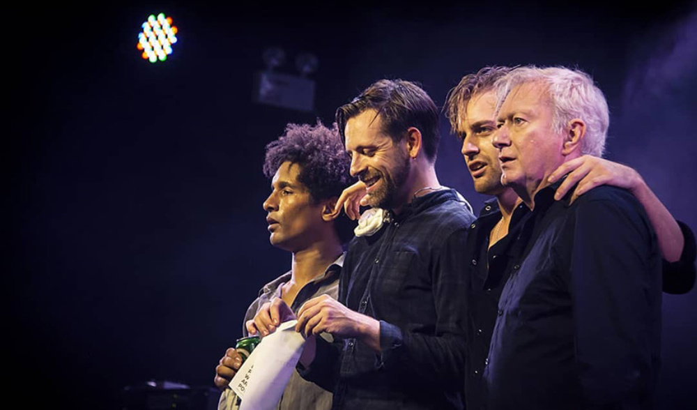Four men stood in a row on stage after a performance with their arms around each other smiling