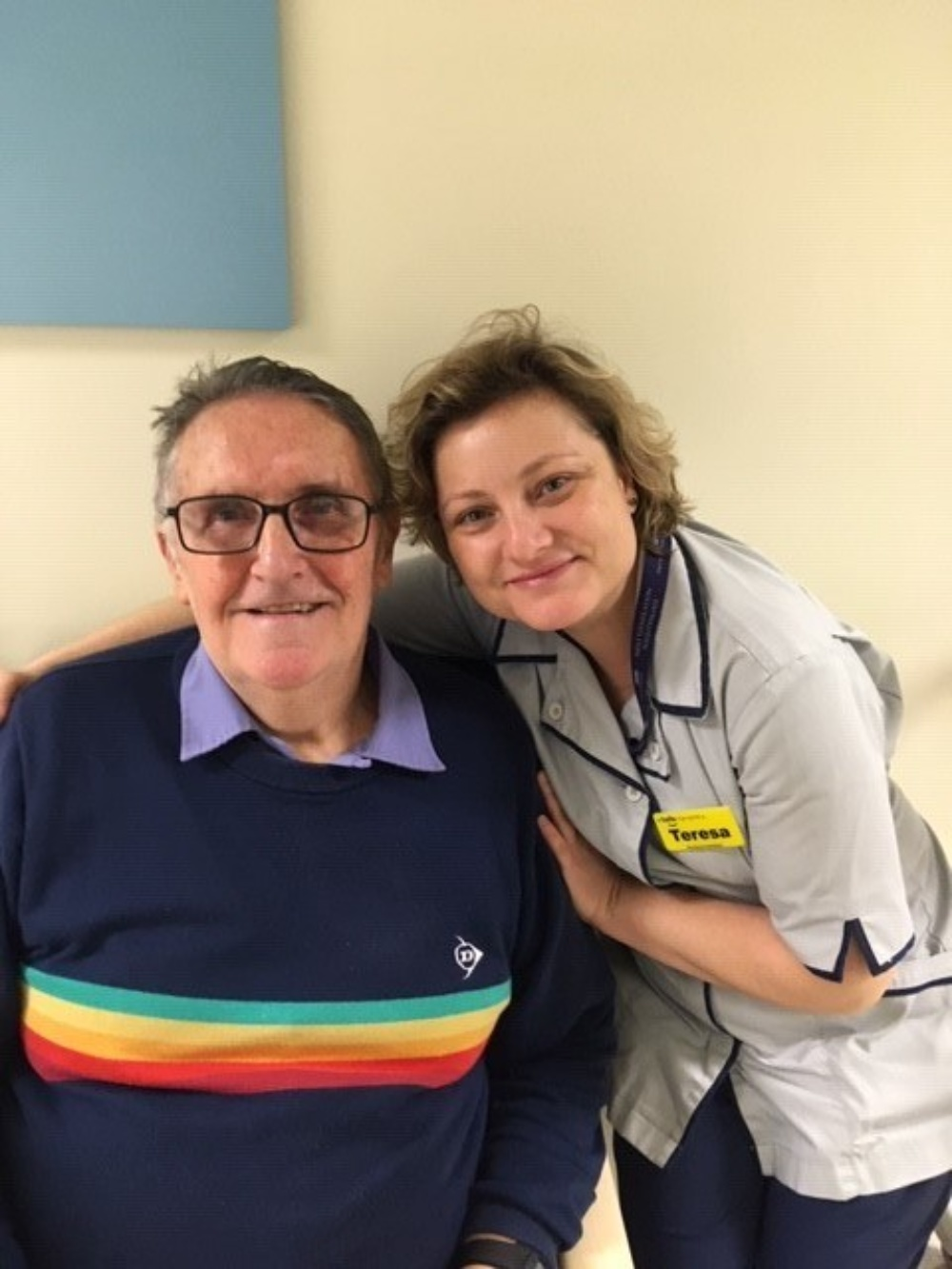 A man smiling at the camera with his nurse next to him