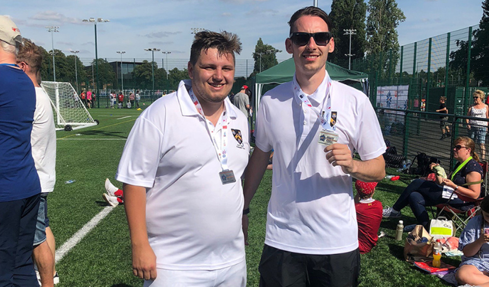 Two friends standing beside a pitch on sports day