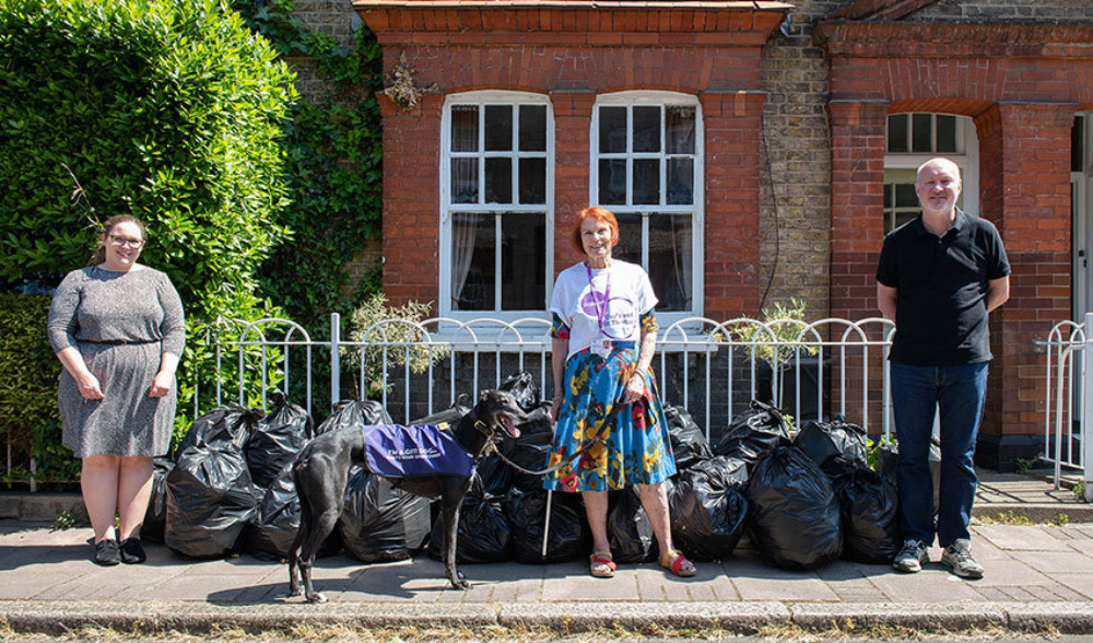 Three adults and a dog, standing outside a house during the day, with 30 filled refuse bags, ready for collection.