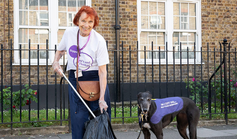 A lady outdoors with her dog, on the street, picking up a piece of litter and placing it into a refuse bag