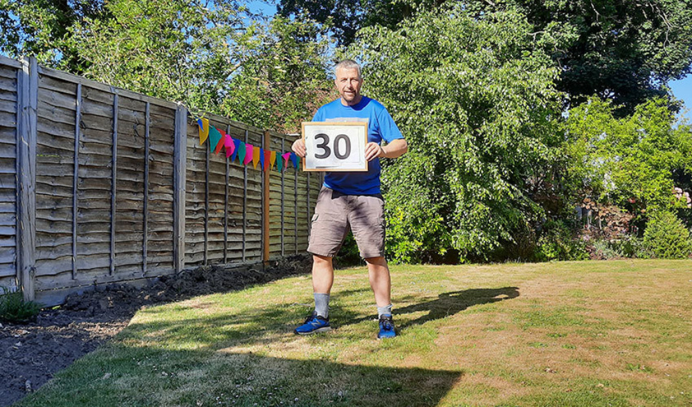 Man in sports gear, walking in his garden holding a sign with 30 on it