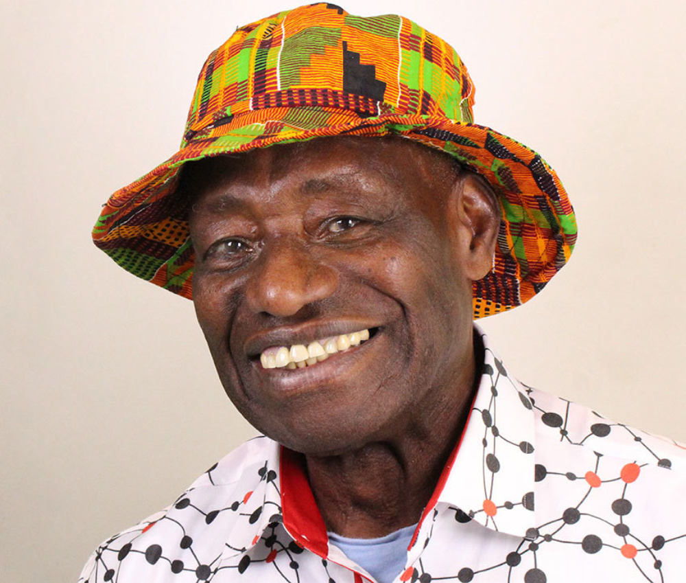 A close up studio shot of a man in a hat smiling towards the camera