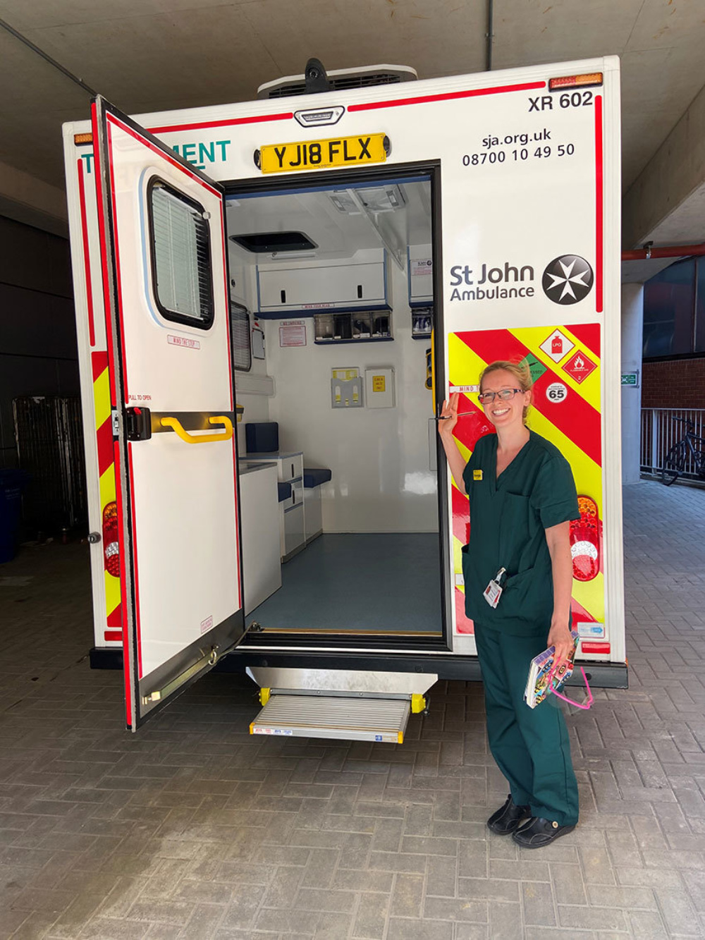 Hospital paramedic standing at the back of an ambulance with one door open, showing the equipment inside
