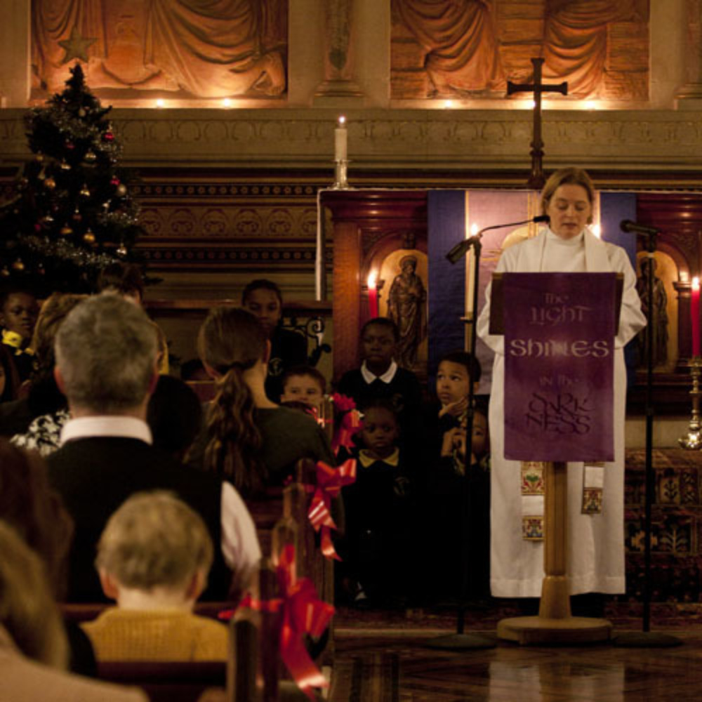 Reverend Mia Hilborn leading the Christmas carols service in 2012