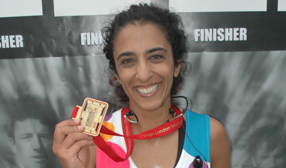 A runner holding her winner's medal at the end of the race
