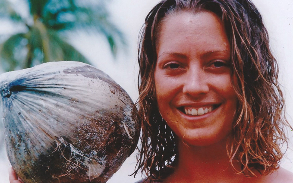 A young lady outdoors on a beach holding a coconut