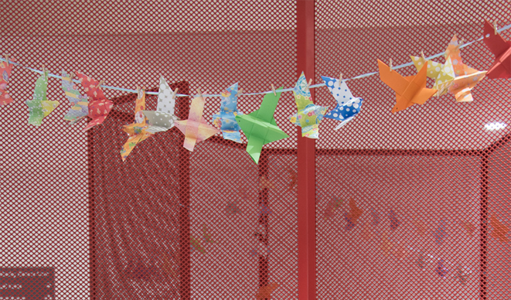 Origami paper birds cut and hung on a string in a reception area