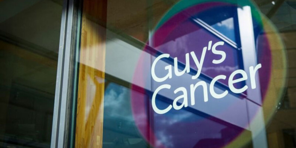 Guy's Cancer words, place within three circles to make up the logo, placed on a glass door entrance